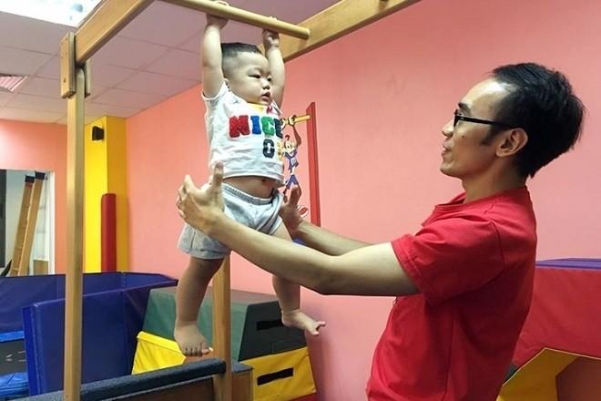Đu xà đơn nhẹ có người lớn bên cạnh giúp bé trai cao to, khỏe mạnh hơn